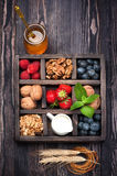 Granola, nuts, berries, honey, milk in wooden box. Royalty Free Stock Photography