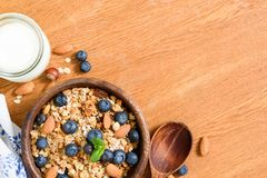 Granola with nuts and berries, milk on wooden table. Top view with copy space for text. Concept of weight loss diet, healthy lifestyle, healthy eating Royalty Free Stock Image