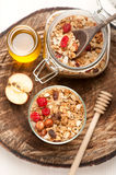Granola with nuts, dried fruit and honey on wooden background Stock Photos