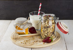 Granola with nuts in glass jar, strawberry, glass of milk. And jar of honey on white wooden table Royalty Free Stock Images