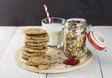 Granola with nuts in glass jar, strawberry, glass of milk, pile. Of oatmeal cookies on white wooden table Stock Image