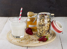 Granola with nuts in glass jar, strawberry, honey jar, glass of. Milk on white wooden table Stock Photo