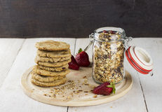 Granola with nuts in glass jar, strawberry, pile of oatmeal cook. Ies on white wooden table Stock Photography