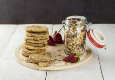 Granola with nuts in a glass jar, strawberry, a pile of oatmeal. Cookies and the crumbled cookies on a white wooden table Royalty Free Stock Image