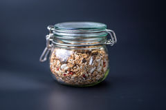 Granola with nuts and seeds in glass jar stock images