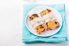 Granola, oatmeal, oat bars with dried cranberry and raisin on a white and blue background. Healthy breakfast Stock Images