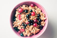 Granola oder Flocken mit Beeren der Schwarzen Johannisbeere und der Stachelbeere in einer rosa Platte auf einem weißen Hintergrun stockfotos