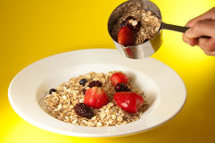Granola Plate. Model using measuring cup to serve organic cereal and fresh strawberries, blueberries and blackberries on a white plate over colorful yellow Stock Photos