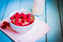 Granola with raspberries in a bowl on wooden background Royalty Free Stock Photos