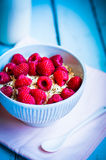 Granola with raspberries in a bowl on wooden background Royalty Free Stock Photo