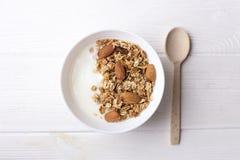 Granola saine de petit déjeuner avec du yaourt grec, miel, écrous de mélange sur la vue supérieure de fond en bois blanc, l'espac images libres de droits