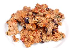 Granola Snack. Made from oats, raisins, almonds, cashewnuts, cranberries, peanuts and maple syrup; isolated on the plate Royalty Free Stock Photos