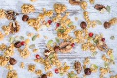 Granola sparso con i dadi sul ripiano del tavolo grungy fotografia stock libera da diritti
