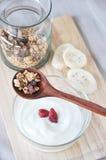 Granola spoon put on yogurt bowl Royalty Free Stock Photo
