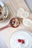 Granola on spoon with yogurt bowl Stock Photos