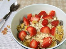Granola and strawberries. A bowl of granola and strawberries on a floral towel stock image
