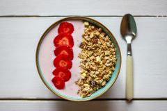 Granola with strawberries on a white wooden backdrop. stock images