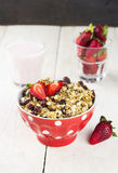 Granola with strawberry and yogurt on a white wooden background.  Royalty Free Stock Photo