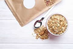 Granola superfood with almond and cashew nuts, dry fruits, raisins cherry in the ceramic jar on the white wooden table, top view,. Granola superfood with almond Stock Photo