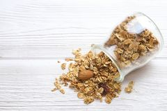 Granola superfood with almond and cashew nuts, dry fruits, raisins cherry in the ceramic jar on the white wooden table, top view,. Granola superfood with almond Royalty Free Stock Photos