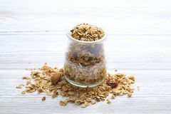 Granola superfood with almond and cashew nuts, dry fruits, raisins cherry in the ceramic jar on the white wooden table, top view,. Granola superfood with almond Stock Photography