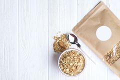 Granola superfood with almond and cashew nuts, dry fruits, raisins cherry in the ceramic jar on the white wooden table, top view,. Granola superfood with almond Stock Photos