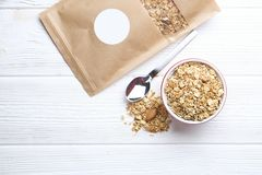 Granola superfood with almond and cashew nuts, dry fruits, raisins cherry in the ceramic jar on the white wooden table, top view,. Granola superfood with almond Royalty Free Stock Images