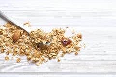 Granola superfood mit Mandel und Acajounüsse, trockene Früchte, Rosinen Kirsche und Löffel auf dem weißen Holztisch, Draufsicht,  Stockbilder