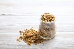 Granola superfood mit Mandel und Acajounüssen, trockene Früchte, Rosinenkirsche im Glasgefäß auf dem weißen Holztisch, Draufsicht Lizenzfreie Stockbilder