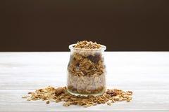 Granola superfood mit Mandel und Acajounüssen, trockene Früchte, Rosinenkirsche im Glasgefäß auf dem weißen Holztisch, Draufsicht Stockfoto