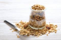 Granola superfood mit Mandel und Acajounüssen, trockene Früchte, Rosinenkirsche im Glasgefäß auf dem weißen Holztisch, Draufsicht Lizenzfreies Stockfoto
