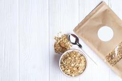 Granola superfood mit Mandel und Acajounüssen, trockene Früchte, Rosinenkirsche im keramischen Glas auf dem weißen Holztisch, Dra Stockfotos