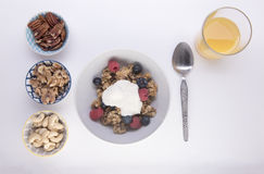 Granola topped with yogurt and portions of mixed nuts Stock Photo