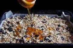Granola in un vassoio di cottura con miele dal lato Immagine Stock