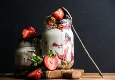 Granola van de yoghurthaver met aardbeien, moerbeibomen, honing en muntbladeren in lange glaskruik op zwarte achtergrond royalty-vrije stock afbeeldingen