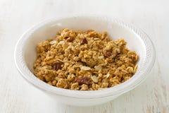 Granola in white bowl on white background Stock Photo