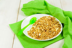 Granola on white plate with green plastic spoon like breakfast f. Or kids on green tissue and white wooden table Royalty Free Stock Photo