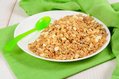 Granola on white plate with green plastic spoon like breakfast f. Or kids on green tissue and white wooden table Stock Images
