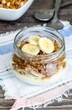 Granola, yogur y un plátano en tarro Imágenes de archivo libres de regalías