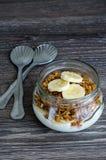 Granola, yogur y un plátano en tarro con dos cucharas Fotografía de archivo libre de regalías
