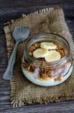 Granola, yogur y un plátano en tarro en el paño rústico Fotos de archivo libres de regalías