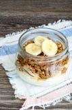 Granola, yogur y un plátano en tarro en el paño rústico Imagen de archivo libre de regalías