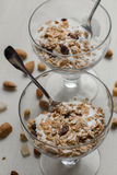 Granola with yogurt, nuts and fruits in glass bowl on light Stock Photos