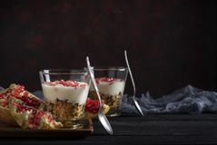 Granola with yogurt and pomegranate on black wooden table stock photos