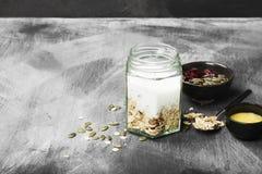 Granola z jogurtem, miód, dokrętki, owoc na ciemnym tle Co Zdjęcie Royalty Free