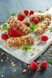 Granolastång med jordgubbar, hallonhonung och vitchoklad på skärbräda Arkivfoto