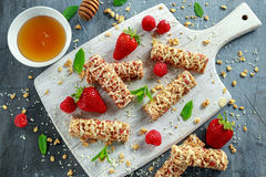 Granolastång med jordgubbar, hallonhonung och vitchoklad på skärbräda Royaltyfri Foto