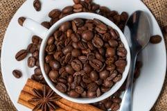 Granos, canela y anís de café en taza de café fotografía de archivo