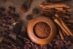 Granos de cacao crudos, chocolate negro delicioso, palillos de canela, sta imagenes de archivo