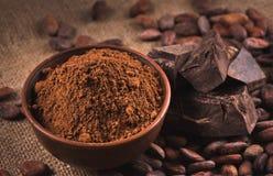 Granos de cacao crudos, cuenco de la arcilla con el polvo de cacao, chocolate en el saco Fotos de archivo libres de regalías